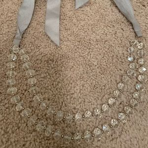Clear beaded necklace with grey ribbon tie back
